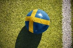 Fußballball mit der Staatsflagge von Schweden liegt auf dem Feld Lizenzfreie Stockbilder