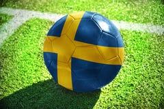 Fußballball mit der Staatsflagge von Schweden liegt auf dem grünen Feld Lizenzfreie Stockfotos