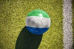 Fußballball mit der Staatsflagge von Sierra Leone liegt auf dem Feld Lizenzfreies Stockbild