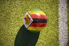 Fußballball mit der Staatsflagge von Simbabwe liegt auf dem Feld Lizenzfreie Stockfotografie