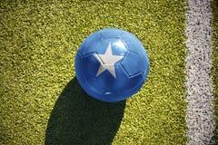 Fußballball mit der Staatsflagge von Somalia liegt auf dem Feld Lizenzfreie Stockfotografie