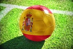 Fußballball mit der Staatsflagge von Spanien liegt auf dem grünen Feld Lizenzfreie Stockbilder