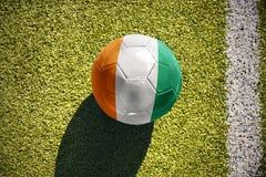 Fußballball mit der Staatsflagge von Taubenschlag divoire liegt auf dem Feld Lizenzfreies Stockfoto