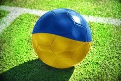 Fußballball mit der Staatsflagge von Ukraine liegt auf dem grünen Feld Lizenzfreies Stockfoto