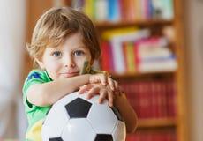 Fußballcupspiel des kleinen Jungen aufpassendes im Fernsehen Lizenzfreie Stockbilder