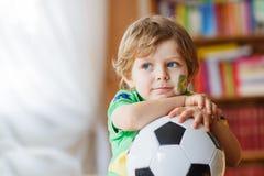 Fußballcupspiel des kleinen Jungen aufpassendes im Fernsehen Lizenzfreie Stockfotografie