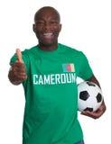 Fußballfan von Kamerun mit dem Fußball, der sich Daumen zeigt Stockbild