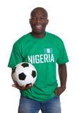 Fußballfan von Nigeria mit dem Ball, der Kamera betrachtet lizenzfreies stockbild