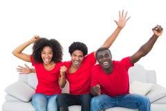 Fußballfane im roten Zujubeln auf dem Sofa lizenzfreie stockfotos