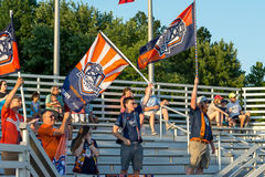 Fußballfans, die Flaggen für ihre Teams wellenartig bewegen Stockfotografie
