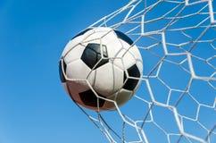 Fußballfußball im Zielnetz mit dem Himmelfeld lizenzfreies stockbild