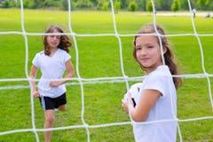 Fußballfußball-Kindermädchen, die auf Feld spielen Stockfotos