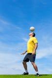 Fußballfußballspieler, der einen Ball mit seinem Kopf schlägt Stockbild