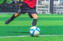 Fußballjungentraining, das den Ball auf dem Fußballtrainingsgebiet tritt stockfoto
