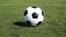 Fußballkugel auf astro Rasen Stockbilder
