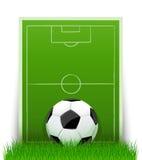 Fußballkugel auf dem grünen Feld mit Gras Stockbild