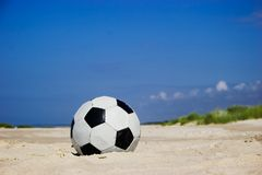 Fußballkugel auf sandigem Strand Stockbilder