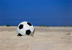 Fußballkugel auf sandigem Strand Stockfotografie