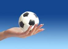 Fußballkugel in der Hand Lizenzfreie Stockfotos