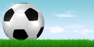 Fußballkugel im Gras mit blauem Himmel Stockfoto