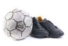 Fußballkugel mit zwei alten schwarzen Schuhen Stockbilder
