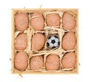 Fußballkugel und -eier in einem hölzernen Kasten lizenzfreies stockbild