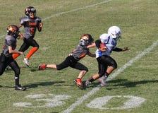 Fußballläufer der Jugend 11u auf Yard-Line 30 stockfotos