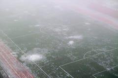 Fußballplatz im Nebel und im schmelzenden Schnee Stockbild