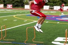 Fußballquertraining durch das Springen von Hürden stockfotos