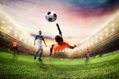 Fußballschlaggerät schlägt den Ball mit einem akrobatischen Fahrradtritt Wiedergabe 3d stockfotos