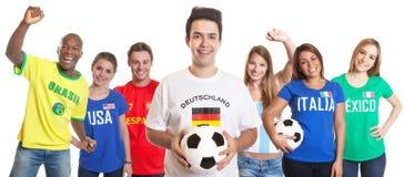 Fußballspieler aus Deutschland mit Fans aus anderen Ländern Stockfotografie
