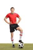 Fußballspieler, der über einen Ball auf Gras tritt Stockfoto
