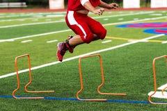 Fußballspieler, der über orange Hürden springt, stockbild