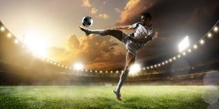 Fußballspieler in der Aktion auf Sonnenuntergangstadions-Panoramahintergrund stockfotografie