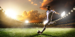 Fußballspieler in der Aktion auf Sonnenuntergangstadions-Panoramahintergrund Lizenzfreie Stockfotos