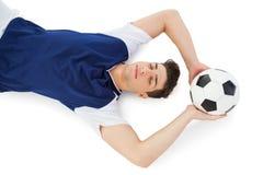 Fußballspieler, der aus den Grund mit Ball liegt Stockfotos
