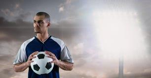 Fußballspieler, der Ball gegen Flutlicht hält Lizenzfreie Stockfotos
