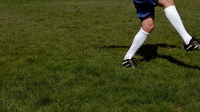 Fußballspieler, der den Ball auf Gras tritt stock video footage