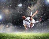 Fußballspieler, der die Kugel schlägt Lizenzfreie Stockfotos