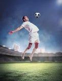 Fußballspieler, der die Kugel schlägt Stockbild