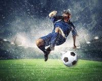 Fußballspieler, der die Kugel schlägt Lizenzfreie Stockfotografie