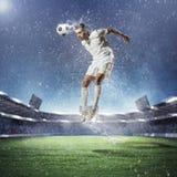 Fußballspieler, der die Kugel schlägt Stockbilder