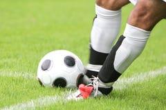 Fußballspieler, der Kugel tritt Stockfotografie