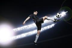 Fußballspieler in der mittleren Luft, die den Fußball tritt, Stadion beleuchtet nachts im Hintergrund Stockfotos