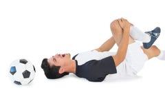 Fußballspieler, der sich hinlegt und in den Schmerz schreit Stockbild