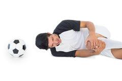 Fußballspieler, der sich hinlegt und in den Schmerz schreit Lizenzfreies Stockfoto