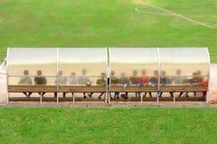 Fußballspieler und -personal sitzt auf Bank neben dem Fußballplatz Lizenzfreie Stockfotografie