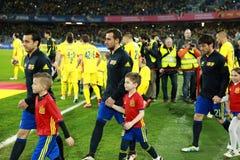 Fußballspieler von Spanien und von Rumänien geben das Feld ein Stockbild