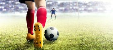 Fußballspielerfrau im orange Trikot, das den Ball in der Strafbank tritt stockfoto