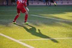 Fußballspielerschatten auf dem grünen künstlichen Fußballplatz Stockbild